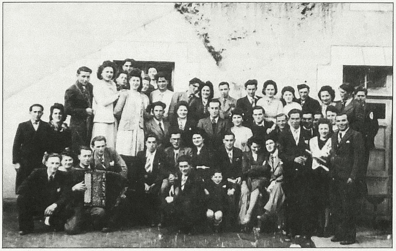 Cerizay (79). Vers 1950. Groupe de jeunes entourant le musicien devant le café Chesseron. Accordéon : Alfred Talon