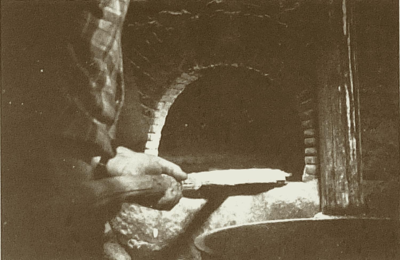 [Cuisson des galettes de Pâques » au four, suite.] Il vérifie que le four est à bonne température en y promenant au bout d'une perche un papier journal, qui doit roussir mais non s'enflammer. Ensuite, il enfourne les galettes, celles de la voisine (3) ou les siennes (4).